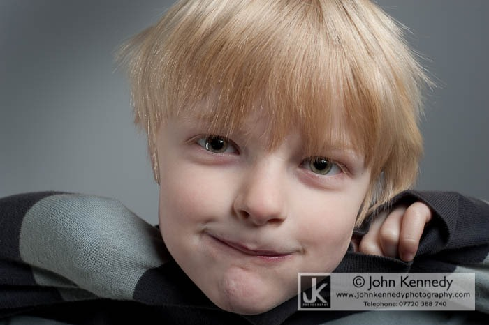 A portrait photograph of a very cheeky young blond boy.